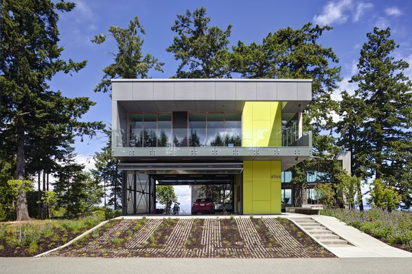 """From the street a vegetated drive bridges the site to the vehicular """"pad"""". From here a semi-enclosed bridge extends through the trees to the wood clad main house beyond. The seasonably closable upper guest house protects the cars in an unconditioned porte-cochere concealed by enormous folding translucent panel doors.   #garage #portecochere #beachhouse #driveway #vegetation #guesthouse #beachhouses #britishcolumbia #limegreen #color #bright #glass #steel #mineralfinish #landscape #green #interstice #intersticearchitects #residential #residentialarchitecture #danlaughton #danlaughtonphotography   Photo 8 of TreeHugger modern home"""