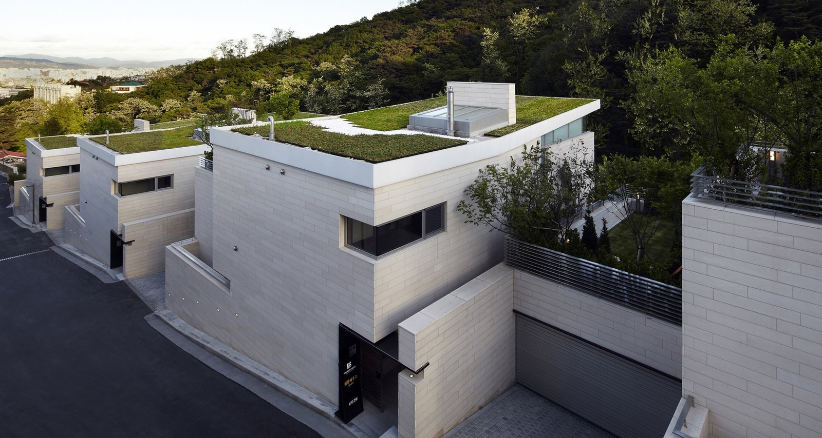 #SeongbukdongResidence #modern #midcentury #enclave #sustainable #L-shaped #exterior #outside #outdoors #structure #rooftop #landscape #green #garage #garden #street #Seoul #JoelSandersArchitects  Seongbukdong Residence by Joel Sanders Architect