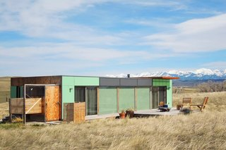 "12 Shipping Container Homes That Challenge the Meaning of Shelter - Photo 1 of 12 - Welcome to the ""Little Box on the Prairie."" This modern house is made from two recycled shipping containers and is situated on 10 acres of rolling prairie land, just North of Livingston, Montana. It's a 700-square-foot mix of rustic coziness and clean, modern design. Many of the finishes, such as the redwood flooring and plywood wall panels, were salvaged off-site, recycled, and reused. The outside deck is perfect for chatting over morning coffee, enjoying an evening glass of wine, gazing at the Absaroka Mountains, and likely spotting a deer or antelope. The house comfortably sleeps two people, and a third can sleep on the sofa, if needed."