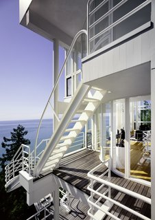 A series of ladders and cantilevered staircases connect each level of home from the exterior, offering a dramatic cascading promenade with an expansive view of Lake Michigan.