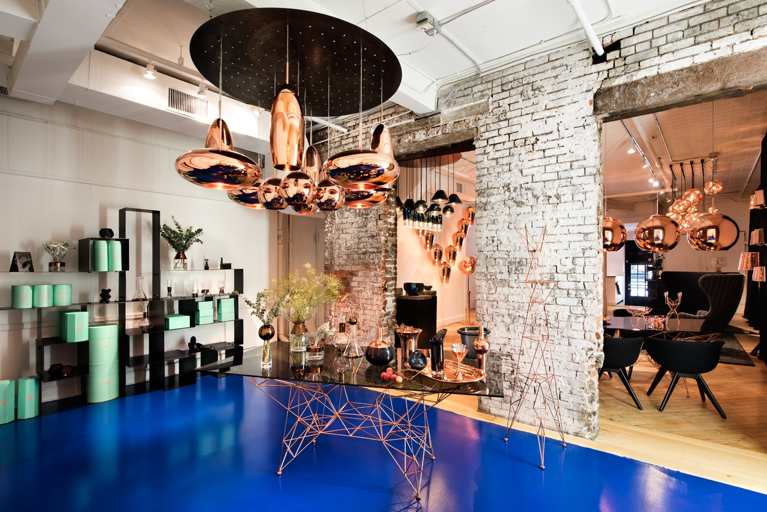 Tom Dixon's new Manhattan showroom at 19 Howard Street, featuring various pendants and tabletop items from the designer's Copper series, and the Pylons dining table, made from a copper-plated steel rod base and smoked glass surface.