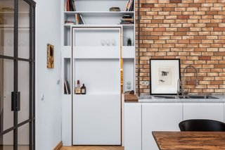 A Hidden Passageway Makes Each Room in This Berlin Flat a Private Destination - Photo 5 of 6 - A view of the pivoting shelf door from the kitchen and dining area.