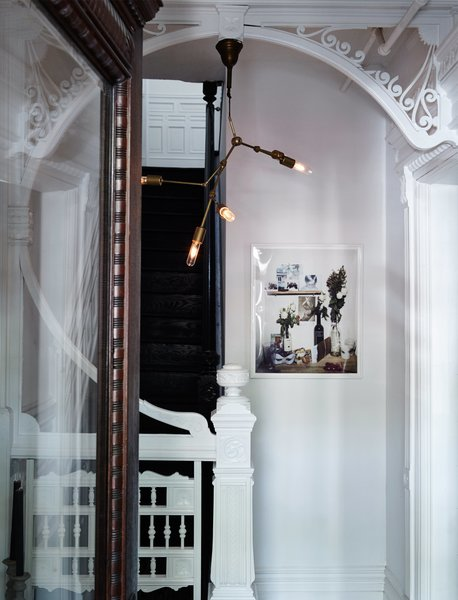 Carefully placed modern touches illuminate restored details in the home. An industrial-style pendant, which Jeff and Jason made themselves using a DIY instructional kit by lighting designer Lindsey Adelman, hangs from the intricate millwork in the entryway. The print is by photographer Anna Wolf.