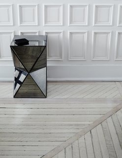 In the downstairs den, the mirrors facets of a West Elm side table refract the linearity of the moulding and hardwood flooring. Removing dated carpeting and vinyl tiles throughout, the couple unearthed and preserved the original wood floor, then sanded, twice bleached, whitewashed, and sealed it to achieve a neutral gray finish.