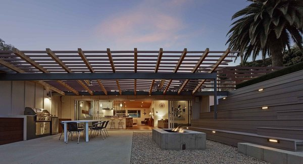 """The rear yard, given the property's limited size, presented more of a conundrum,"" says Southerland. ""We came up with the idea of using the roof of the garage as a roof deck to add useable area to the rear."" Taking advantage of the gently sloped site, he built a series of terraced bleacher-style seating above and around the detached garage, doubling its roof as an additional terrace, and effectively bridging the backyard space into one multi-level whole."