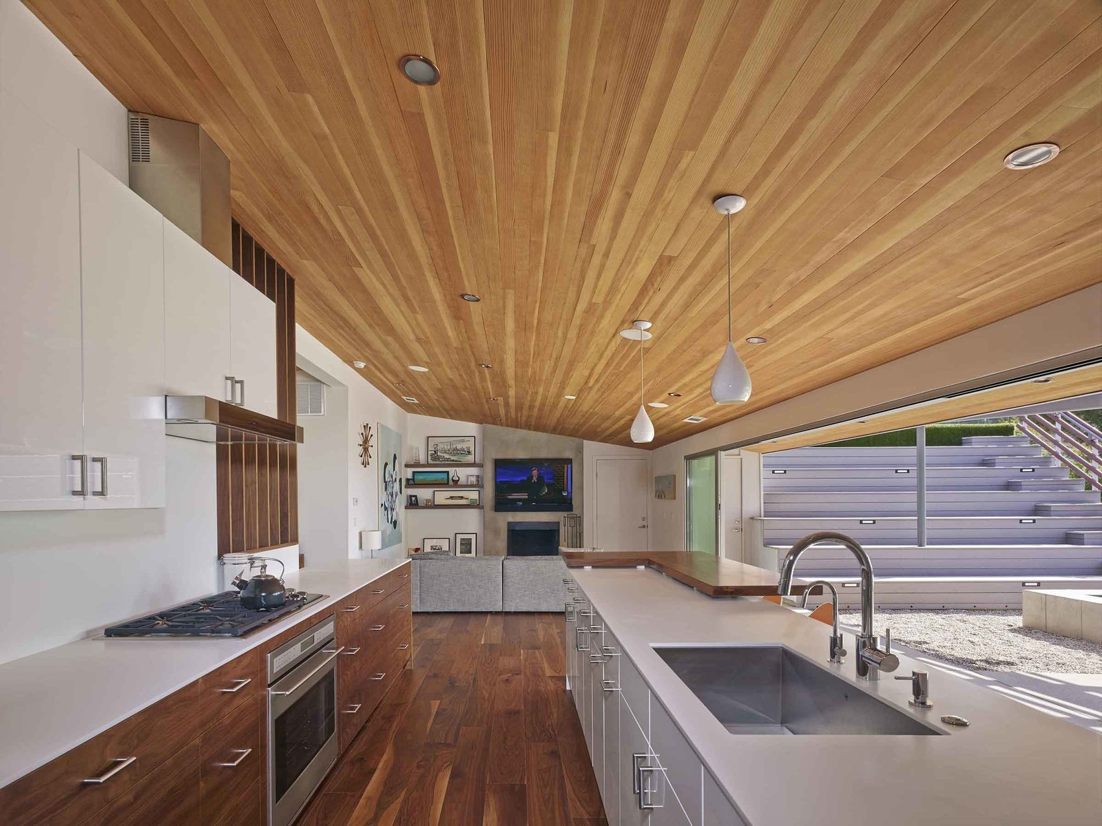"""""""By removing a few interior walls, reconfiguring a couple of others and opening up the kitchen/living/dining areas, we were left with a wonderfully livable floor plan with a great balance of public and private space,"""" says Southerland. A large, open galley style kitchen and mirrored planes of wall paneling visually expand the home's interior perspective."""