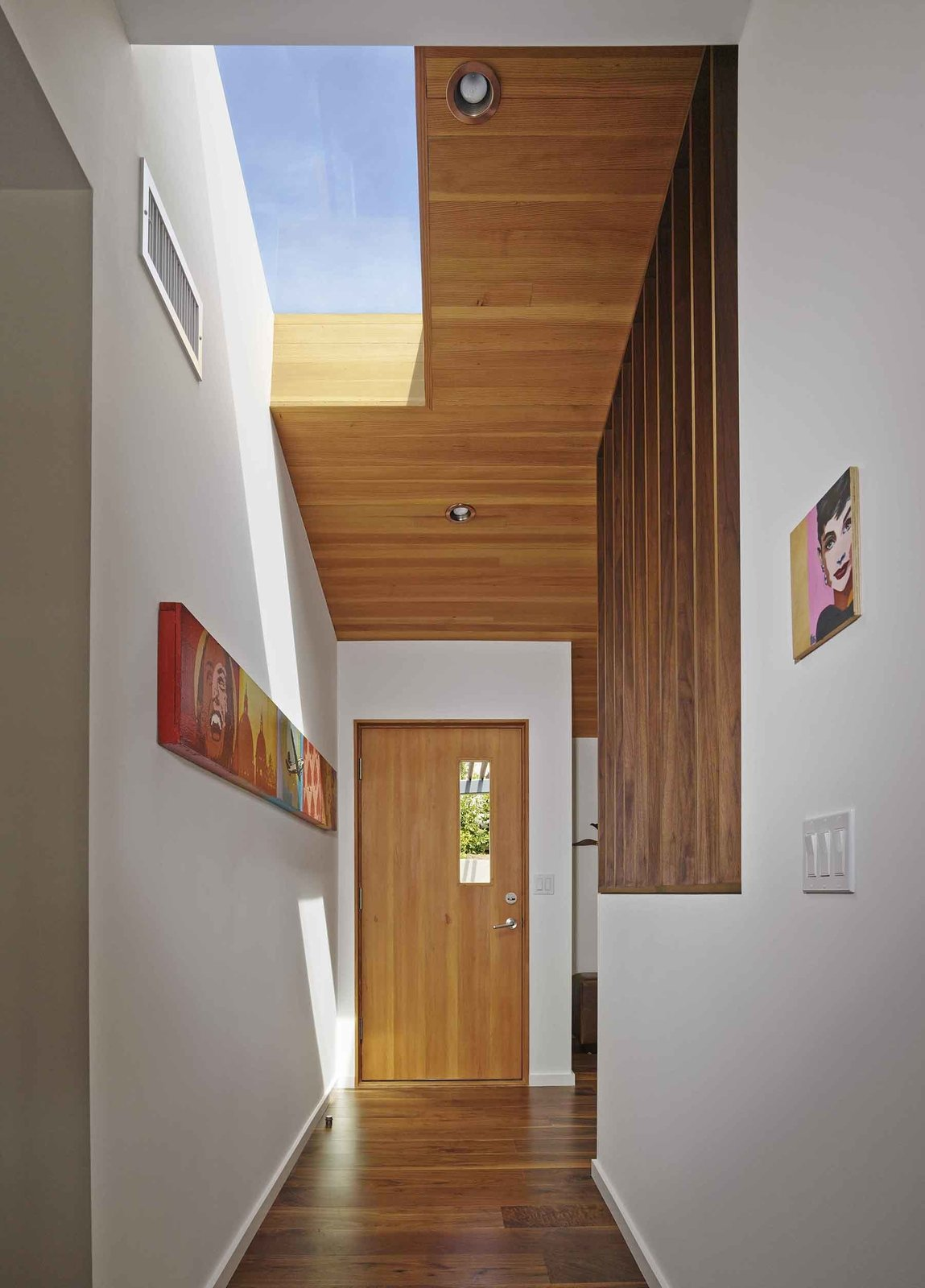 Striated wood paneling and new skylights give dimension to the renovated entryway.
