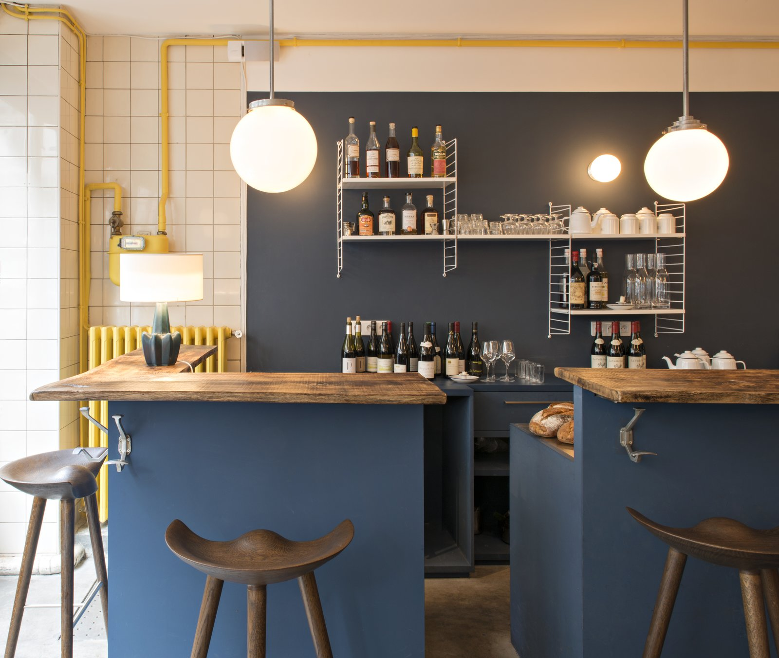 A set of wall-mounted String shelves, an iconic 1949 design by Nisse Strinning, provides storage for the casual bar, which features stools from By Lassen and wooden countertops.  Photo 4 of 6 in A Parisian Seafood Restaurant, Swimming in Shades of Blue