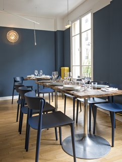 A Parisian Seafood Restaurant, Swimming in Shades of Blue - Photo 5 of 5 - Sixty-five seats are accommodated across Belle Maison's two floors. Bonaventure worked with craftsmen to create the custom chestnut-top tables; the circular wall sconces are vintage.