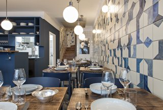 A Parisian Seafood Restaurant, Swimming in Shades of Blue - Photo 4 of 5 - The hand-painted ceramic tile wraps along the wall and continues up the stairwell. Named after Belle Maison, after the owners' favorite beach, the restaurant is focused on seafood dishes.