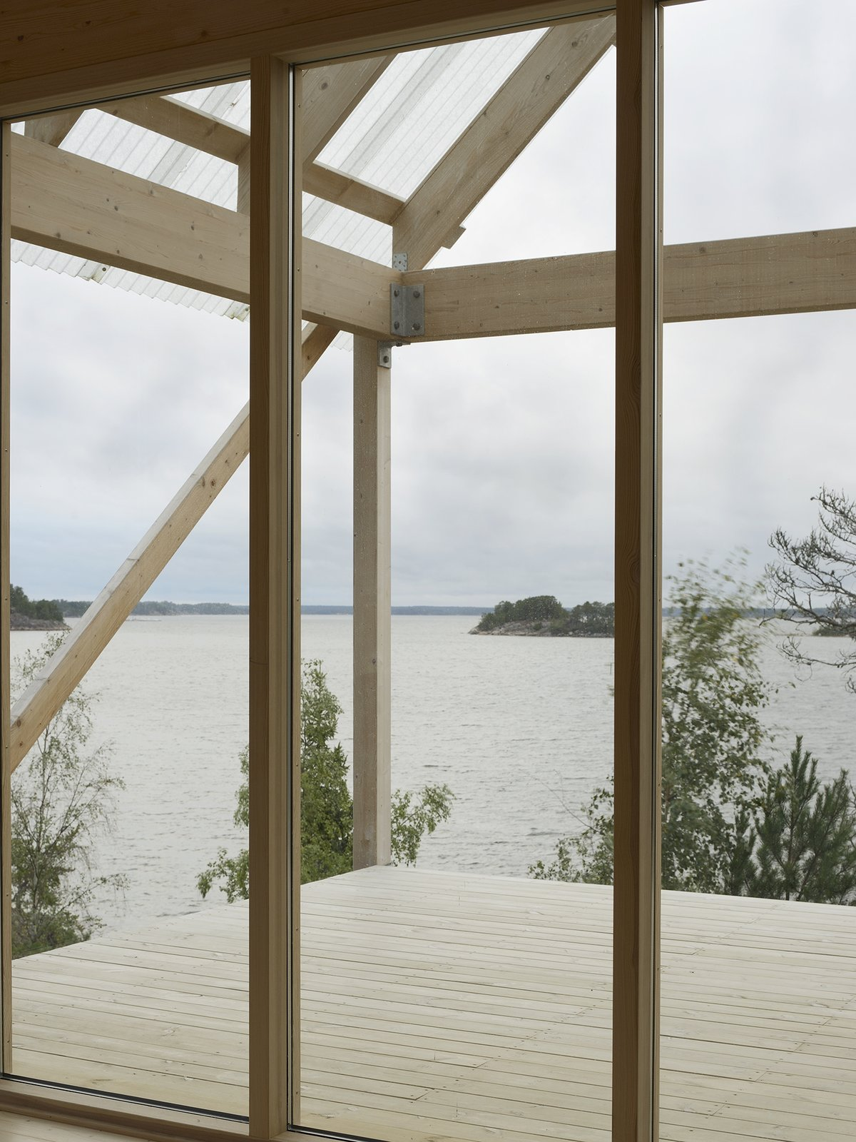 The roof portion made of corrugated fiber-reinforced plastic hangs above deck, which measures roughly 215 square feet and overlooks views of the water.  Photo 3 of 7 in A Swedish Summer Cabin That Sits  Above and Among the Trees