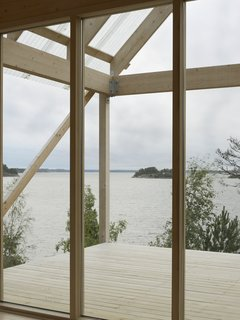 A Swedish Summer Cabin That Sits  Above and Among the Trees - Photo 2 of 6 - The roof portion made of corrugated fiber-reinforced plastic hangs above deck, which measures roughly 215 square feet and overlooks views of the water.