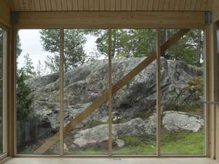 A Swedish Summer Cabin That Sits  Above and Among the Trees - Photo 4 of 6 - A simple timber frame and wide expanses of glass enhance the structure's connection to Viggsö's varied terrain, marked by rocky cliffs, wild-bent pine trees, heather, and lichen.