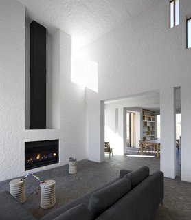 A Minimalist Retreat at the Edge of South Africa's Karoo Desert - Photo 2 of 6 - Soaring ceilings and a fireplace mark the home's main living area.