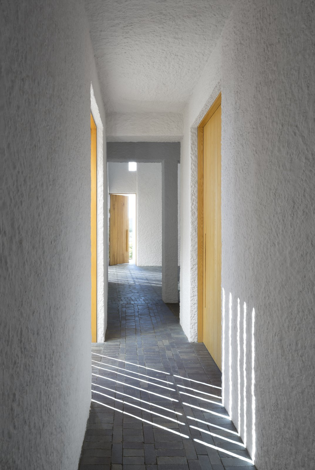 By day, the home's rectilinear windows cast an artful composition of linear shadow and light.