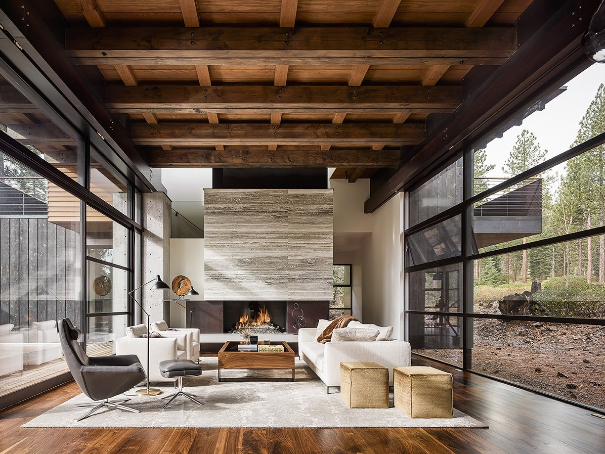 The 5,700-square-foot getaway features glazed screens surrounding the living and dining areas. Tagged: Living Room, Wood Burning Fireplace, Standard Layout Fireplace, Medium Hardwood Floor, Chair, and Sofa.  Photo 3 of 6 in A Family's California Ski Retreat is Designed to Blend in With Its Site