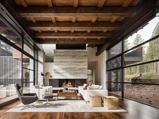 A Family's California Ski Retreat is Designed to Blend in With Its Site - Photo 2 of 5 - The 5,700-square-foot getaway features glazed screens surrounding the living and dining areas. A travertine marble slab fireplace anchors the space; the floors are California walnut.