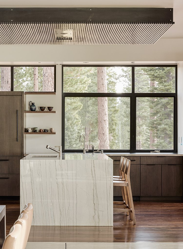 The dining area features ebonized quarter-sawn oak cabinetry with travertine work surfaces. Tagged: Kitchen, Medium Hardwood Floor, and Marble Counter.  Photo 4 of 6 in A Family's California Ski Retreat is Designed to Blend in With Its Site