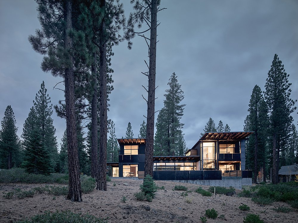 The structure is divided into two solid vertical volumes connected by glazed living areas. The cedar cladding and steel panels reflect the hues of the surrounding forest. Tagged: Exterior, Cabin Building Type, House, and Shed RoofLine.  Photo 6 of 6 in A Family's California Ski Retreat is Designed to Blend in With Its Site