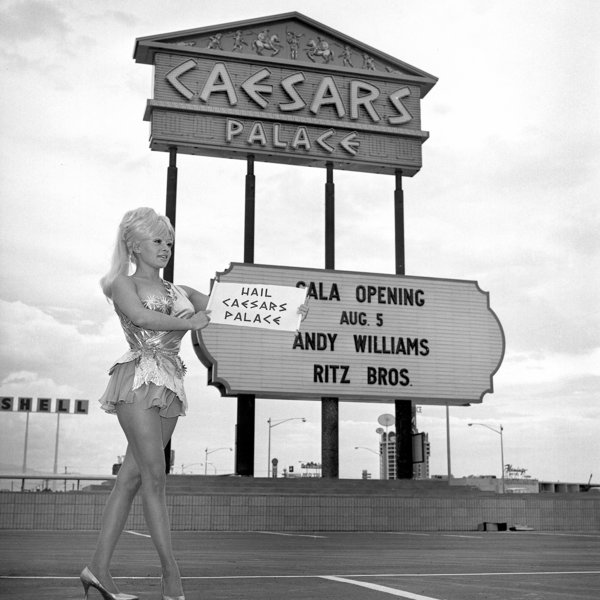 A Caesars Palace employee poses by the themed marquee, created byAd-Art based on a design by the famous Young Electric Sign Design Company, prior to the hotel's grand opening.
