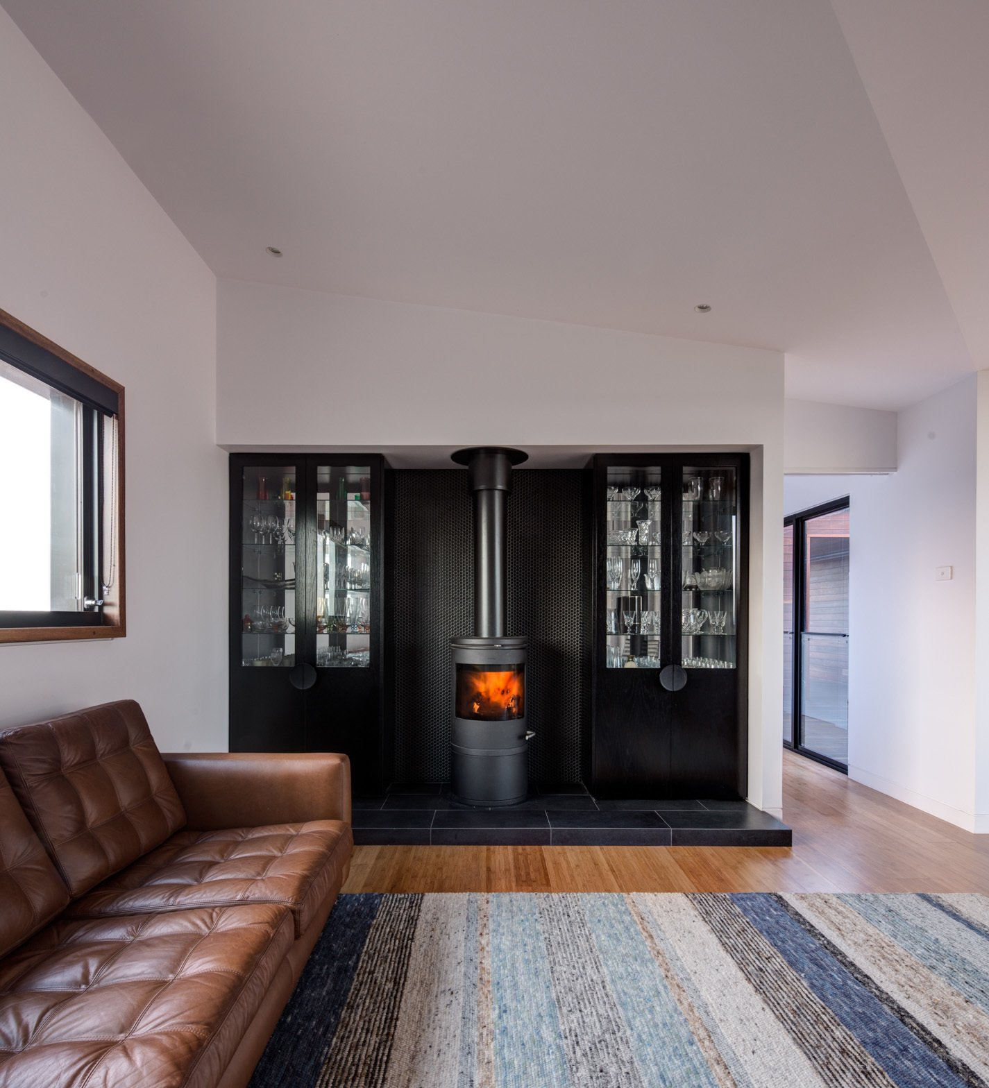 A Morso space heater warms the living room, which features a rug from Halcyon Lake.  Photo 6 of 7 in It Took Three Days to Ferry This Off-the-Grid Prefab to Its Remote Australian Site
