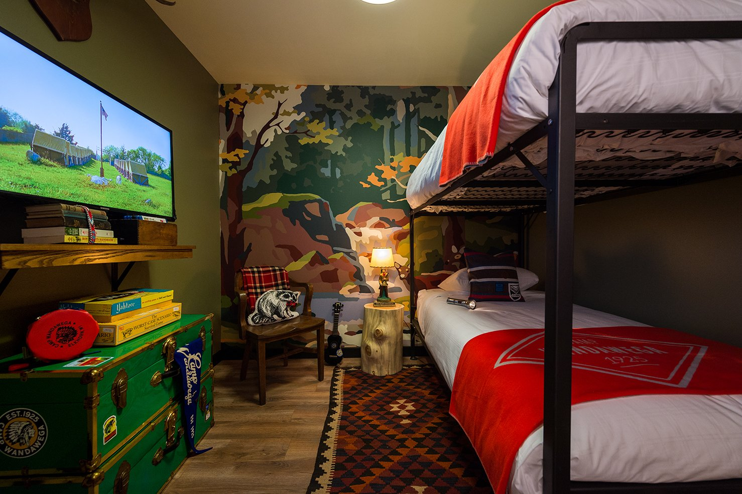 The media room features custom-designed bunks with Camp Wandawega for Land of Nod bedding. Tagged: Bedroom, Bunks, Rug Floor, Medium Hardwood Floor, Night Stands, Lamps, and Shelves.  Photo 2 of 10 in This Wisconsin Hotel Suite Conjures the Best of Summer Camp—Hold the Bug Spray