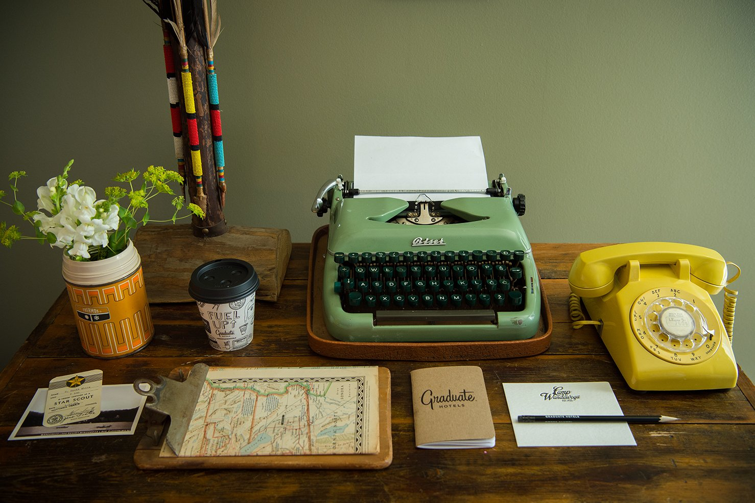 A working vintage typewriter and telephone top the antique desk. Tagged: Office and Desk.  Photo 6 of 10 in This Wisconsin Hotel Suite Conjures the Best of Summer Camp—Hold the Bug Spray