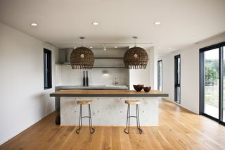 This Minimal Japanese Getaway Was Built for Surfing - Photo 6 of 7 - The kitchen island is made of concrete with an oak top and black steel edging—an industrial element within a project that celebrates nature.