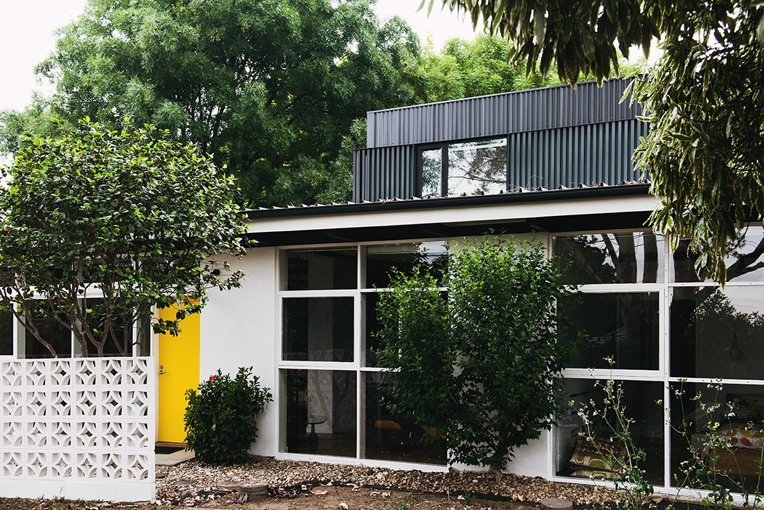 When tasked with renovating a house near Melbourne, the team at Nest Architects decided to honor its midcentury bones while modernizing it for today's residents. The yellow hue on the front door is a detail picked up from the original design. Tagged: Exterior, Metal Siding Material, Stucco Siding Material, and House.  Midcentury Homes by Dwell from An Australian Renovation Gives New Life to Midcentury Style