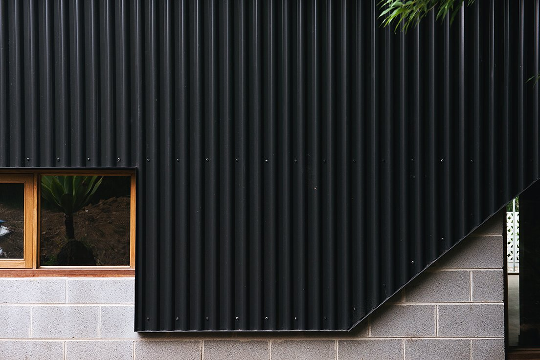 New black metal cladding joins cinderblock and wood-trimmed windows, two features more in line with the home's vintage.  Photo 9 of 15 in An Australian Renovation Gives New Life to Midcentury Style