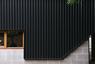 New black metal cladding joins cinderblock and wood-trimmed windows, two features more in line with the home's vintage.
