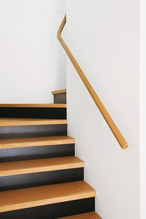 Even the stairs reflect the materials at the heart of the project with their blend of cork, timber, and black against a white backdrop.