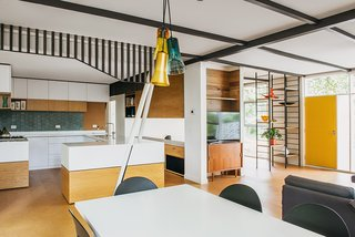 The black framework separating the kitchen and dining area was meant to echo the exterior cladding. Additional black details give the space a grounding geometry.