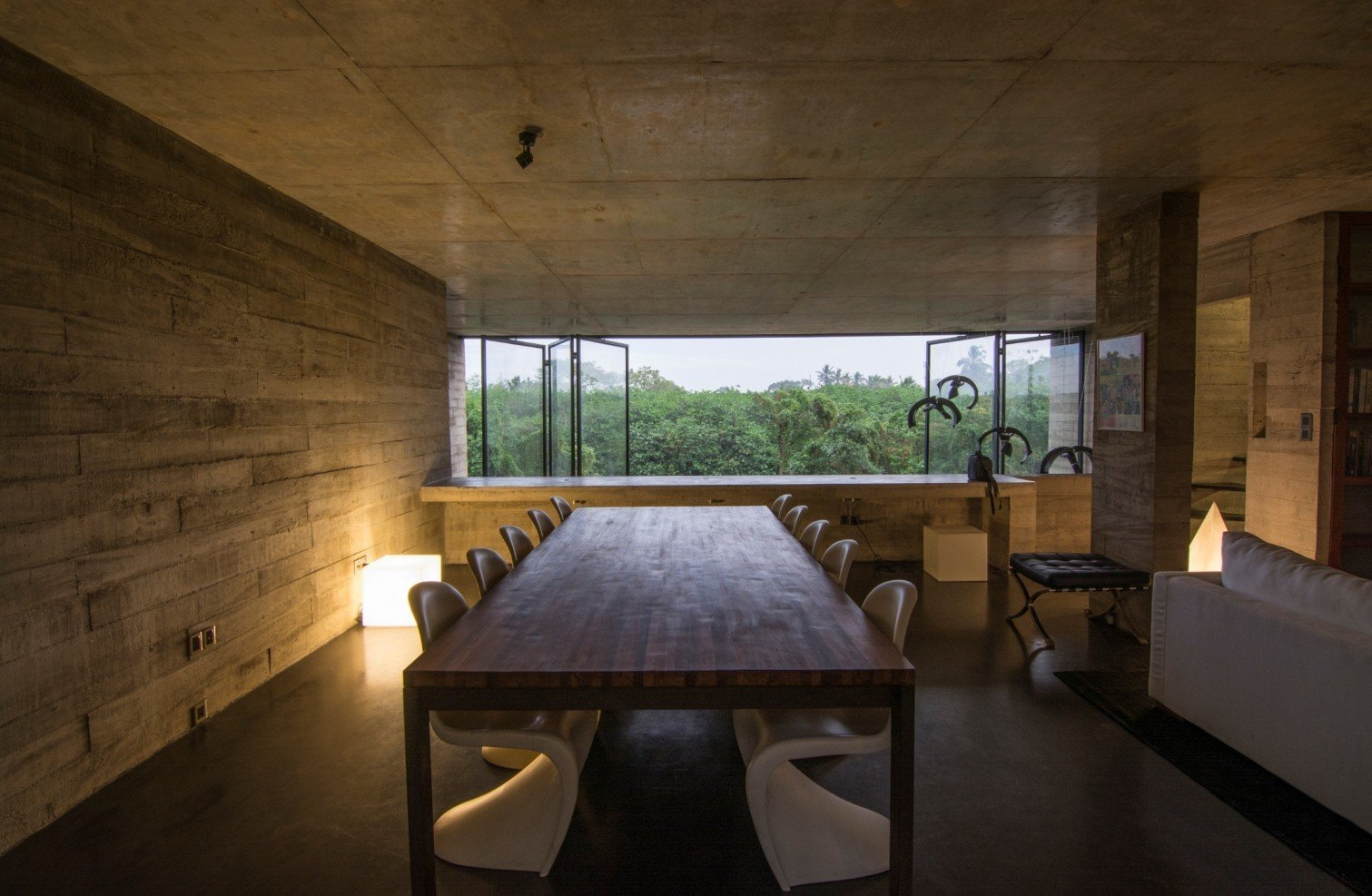 Expanses of low-e glass open to views of the nearby greenery. Tagged: Dining Room, Table, Chair, and Floor Lighting.  Photo 3 of 7 in An Architect's Home and Studio Rises Above Rajagiriya