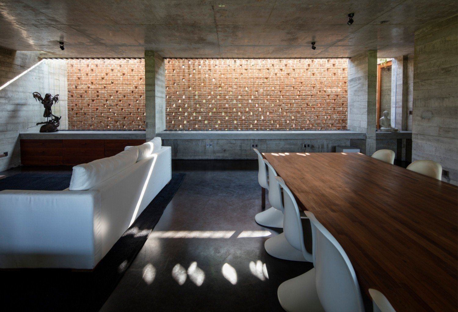 The perforated brick walls aid with heat management. Tagged: Dining Room, Chair, Table, and Concrete Floor. An Architect's Home and Studio Rises Above Rajagiriya - Photo 4 of 7