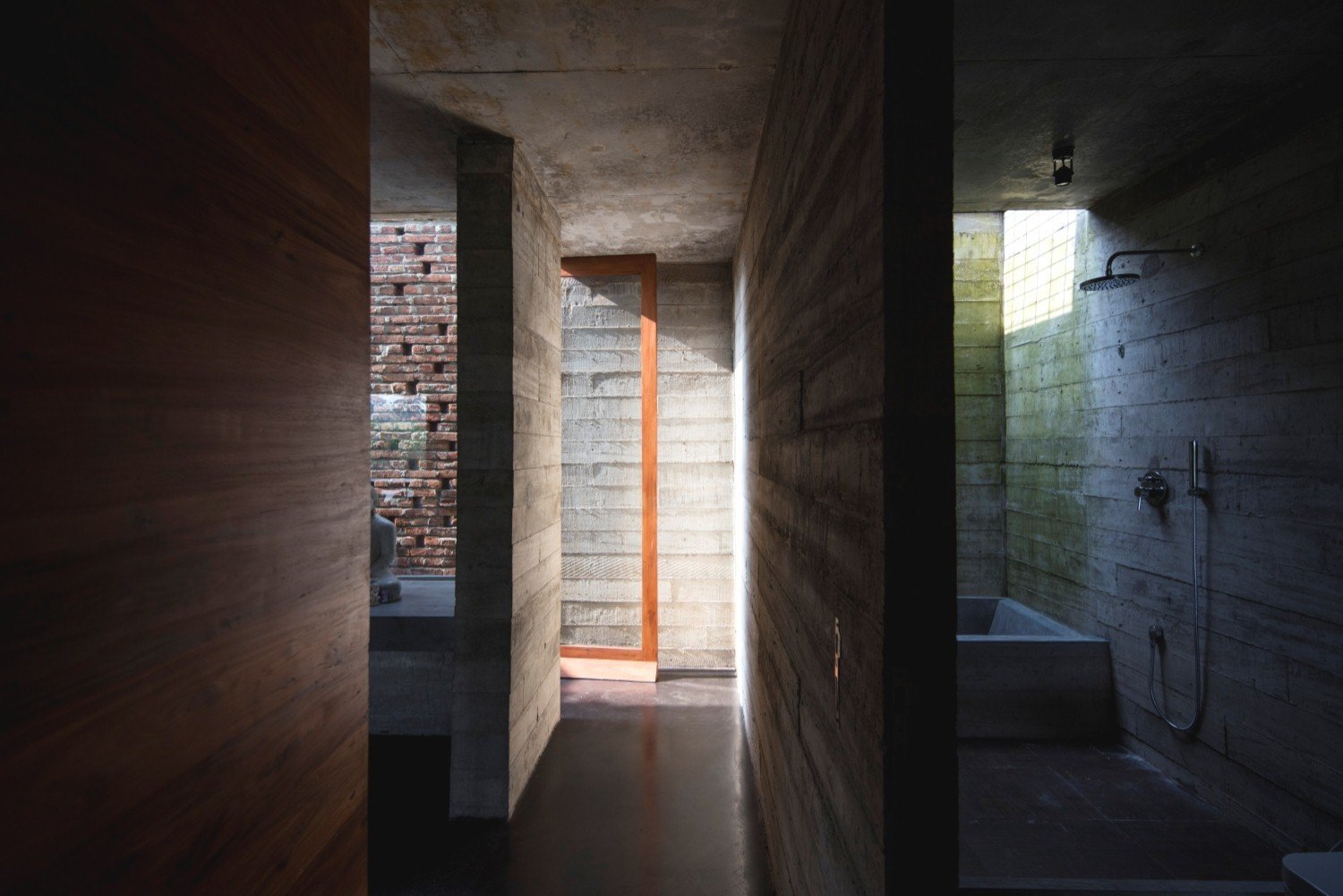 Brick and board-formed concrete are the primary materials of the rugged, yet elegant, structure. Tagged: Bath Room, Open Shower, Concrete Wall, and Concrete Floor.  Photo 6 of 7 in An Architect's Home and Studio Rises Above Rajagiriya