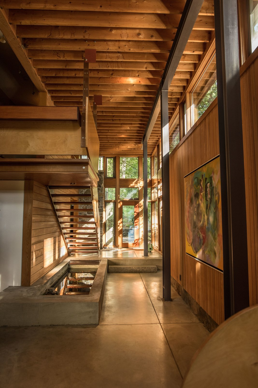 The new spaces recall the original design with their use of natural materials like wood and stone. Tagged: Hallway and Concrete Floor.  Photo 3 of 4 in This Updated Breuer House Could Be Yours for a Cool $2.3 Million