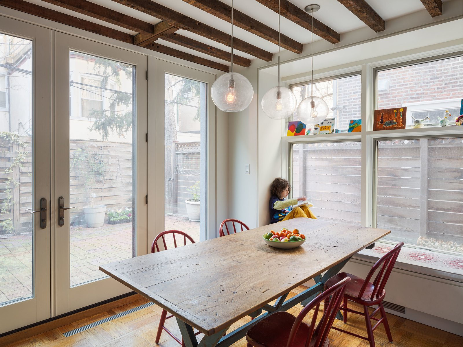 Dark beams contrast the glazing that fills the dining area with light, continuing the home's historic/modern mix. Tagged: Dining Room, Table, Pendant Lighting, Chair, and Medium Hardwood Floor.  Photo 6 of 9 in Philadelphia Row House Renovation