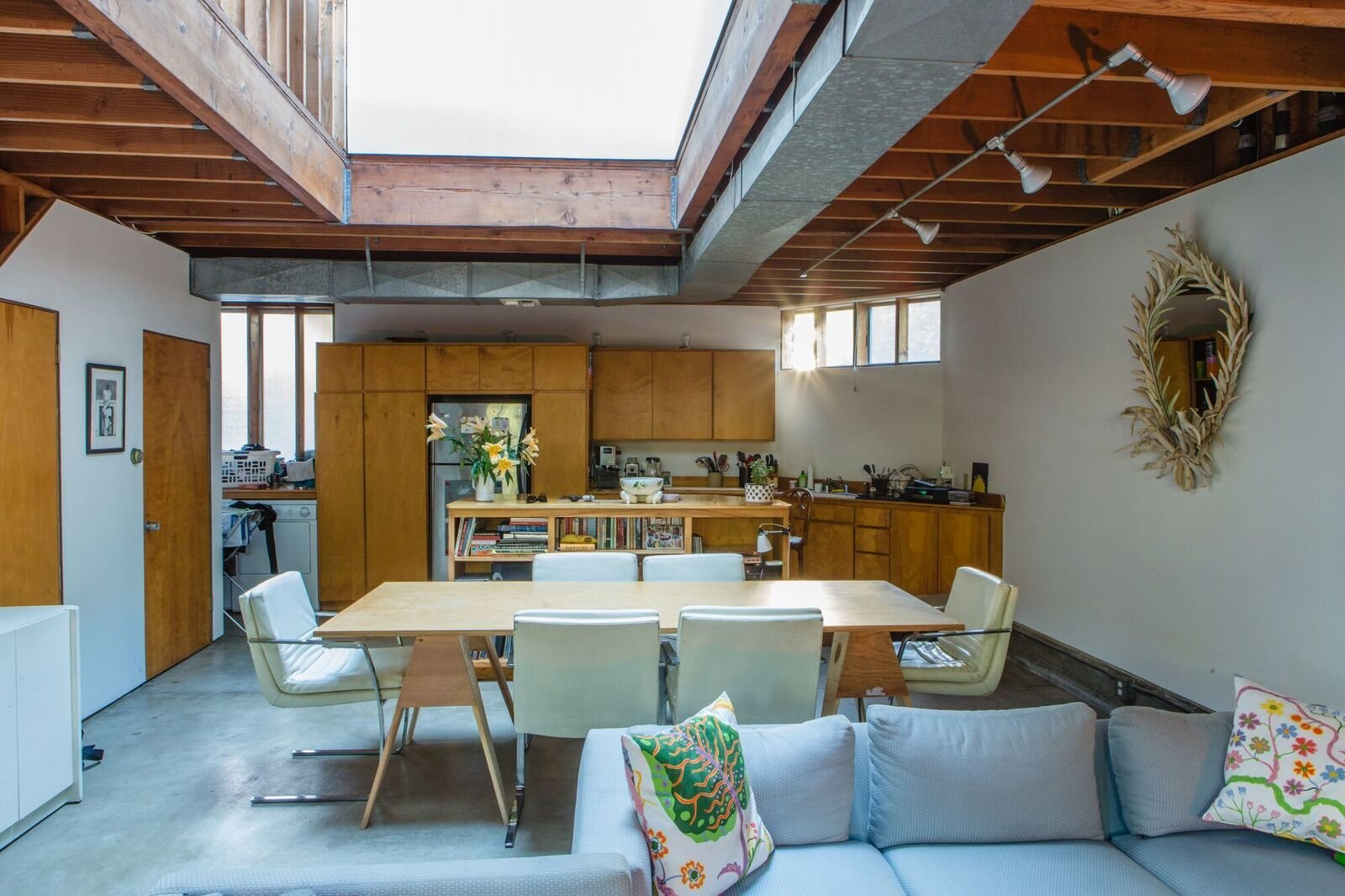 When renting an apartment in Frank Gehry's Spiller House, Kristin Grant Fowler and William Fowler chose simple furnishing that relate back to the architect's humble material palette. The tabletop is set on Burro Brand saw horses—the same ones Gehry uses in his office. The sofa was designed by Kristin's grandfather, Park Avenue interior designer Hector Grant; the mirror was also a gift from him. The cushions are by Josef Frank.  Photo 3 of 12 in Peek Inside the Frank Gehry Rental of an Emerging L.A. Furniture Designer