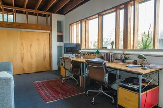 """Vintage Soft Pad chairs by Charles and Ray Eames for Herman Miller (an eBay find) and matching new Eames desk and storage units, also from Herman Miller, furnish a workspace on the mezzanine level. """"When we're both at home we speak to each other all the time,"""" William says of the openness of the house."""