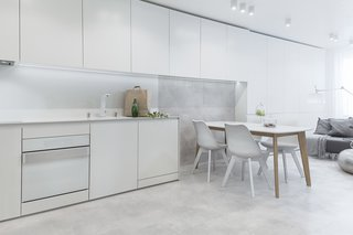 White appliances by Karim Rashid for Gorenje pair with concrete floors in the apartment's kitchen.