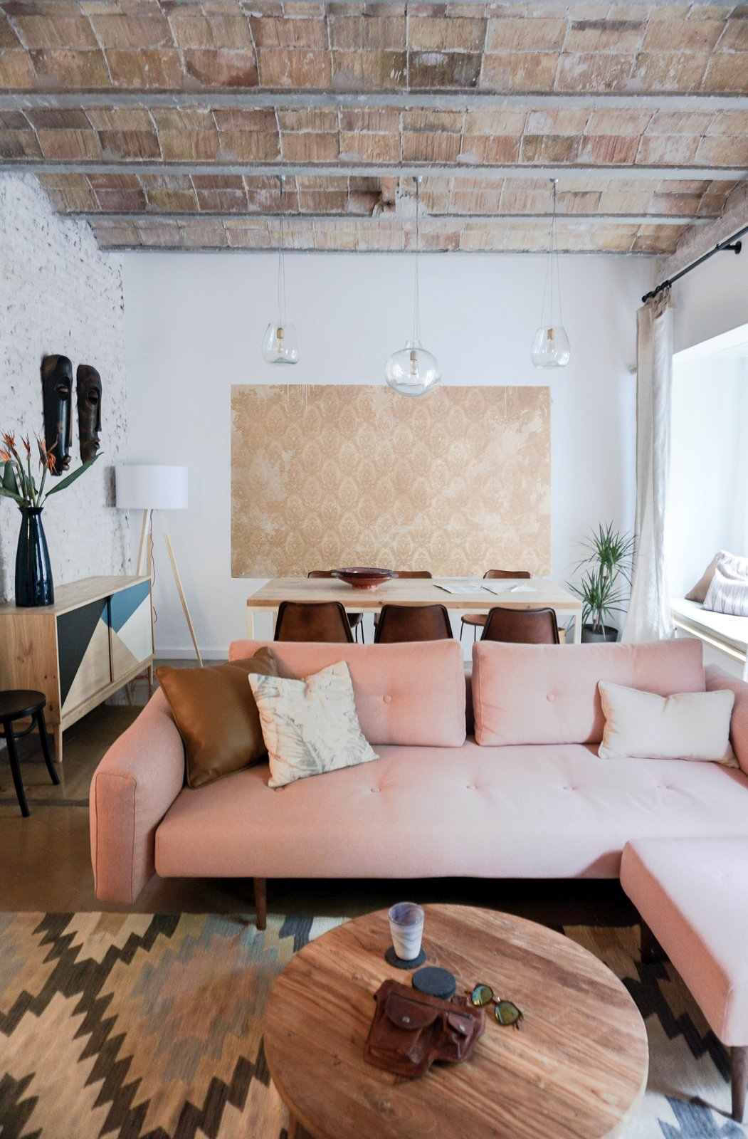To make the space feel brighter, all of the walls—even bricks—are painted white, which contrasts with the raw brick ceiling and original brown tile floors. The Recast Plus sofa bed, with a pink hue that echoes the brick ceiling, is from Innovation Living. The blown-glass Gordiola pendants are a design the resident saw in a Mallorca hotel that Bloomint designed. A Barcelona Apartment Gets a Softly Modern Renovation - Photo 2 of 9