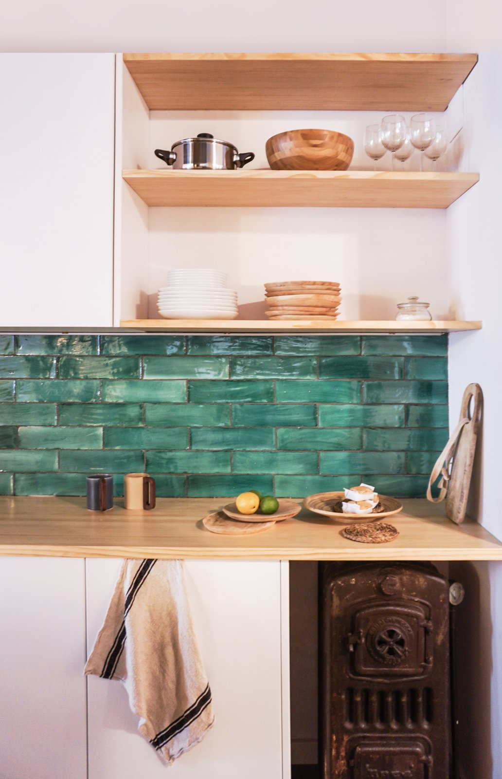 An original boiler the designers discovered during the renovation was kept in the kitchen as decoration. The counter is white pine, and the green tiles were sourced from Can Benito a studio in Mallorca.