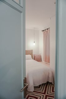 A Barcelona Apartment Gets a Softly Modern Renovation - Photo 5 of 8 - The original doors were salvaged and given a fresh coat of blue paint. The resident brought many of the rugs were from Egypt.