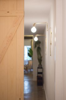 """A Barcelona Apartment Gets a Softly Modern Renovation - Photo 6 of 8 - Once dark and """"spooky,"""" the narrow hallway is now illuminated with LED lights chosen for their warm color. Diffused glass helps soften the glow."""