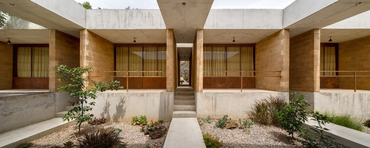 The materials—concrete, stone, and brick—reference the local architecture, tying the house to its site and making it easier to find a construction team. An Eco-Friendly Getaway Built With the Future in Mind - Photo 4 of 8