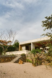 An Eco-Friendly Getaway Built With the Future in Mind - Photo 4 of 7 - The concrete-and-brick house is perched on a stone wall.