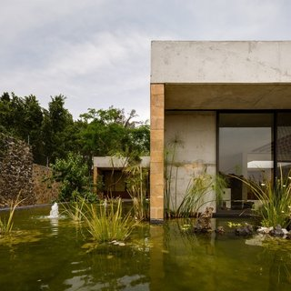 An Eco-Friendly Getaway Built With the Future in Mind - Photo 1 of 7 - Located outside of Mexico City, Casa GP by architecture firm Ambrosi | Etchegaray integrates the local landscape with features like this pond.