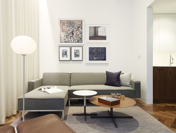 The living room features a 12-foot-high ceiling, which drops to 8.5 feet in other areas of the apartment—an design feature architect and resident Christopher Kitterman used to organize the space. Behind the curtain, sliding glass doors open to a small terrace. The artwork includes a pair of Cindy Sherman prints, a framed Hermès scarf, and two of Kitterman's own photographs.