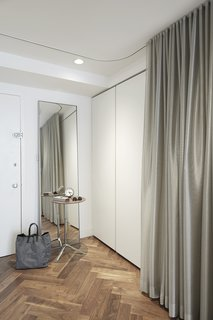 In Just 450 Square Feet, A New York Architect Crafts a Multifunctional Apartment of His Own - Photo 5 of 10 - By the entrance, a silver curtains in KnollTextiles fabric hide a Poliform storage system and a Murphy bed.